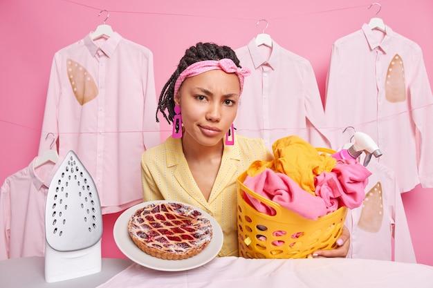 Ontevreden afro-amerikaanse huisvrouw die thuis bezig is met koken, wassen en strijken, poseert voor huishoudelijke taken tegen gestreken kleding die aan touw hangt bij het bord.