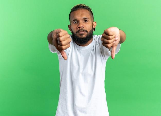 Ontevreden afro-amerikaanse jongeman in wit t-shirt kijkend naar camera met serieus gezicht met duimen naar beneden over groene achtergrond