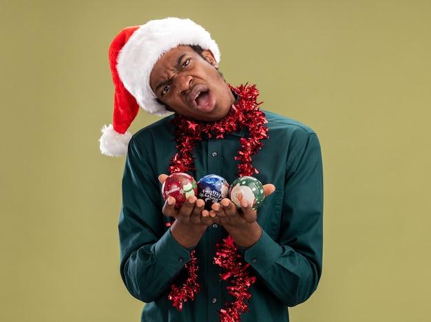 Ontevreden afro-amerikaanse man in kerstmuts met slinger houden kerstballen camera kijken met verwarren uitdrukking staande over groene achtergrond