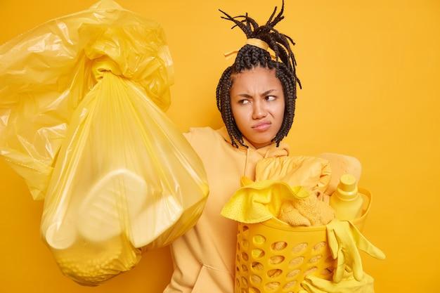 Ontevreden afro-amerikaanse vrouw met dreadlocks houdt polyethyleen tas vast
