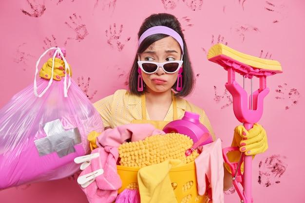 Ontevreden aziatische dame maakt rommelige kamer schoon na feest kijkt verdrietig naar vuilniszak ziet er moe uit terwijl het schoonmaken van huis houdt dweil draagt trendy zonnebril poses in de buurt van wasmand tegen vuile muur
