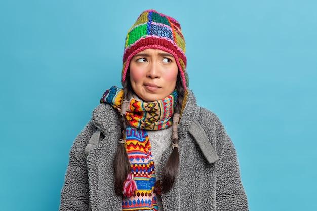 Ontevreden aziatische vrouw fronst haar wenkbrauwen en kijkt ongelukkig opzij, draagt winterkleding, denkt na over het oplossen van probleem vormt tegen blauwe muur