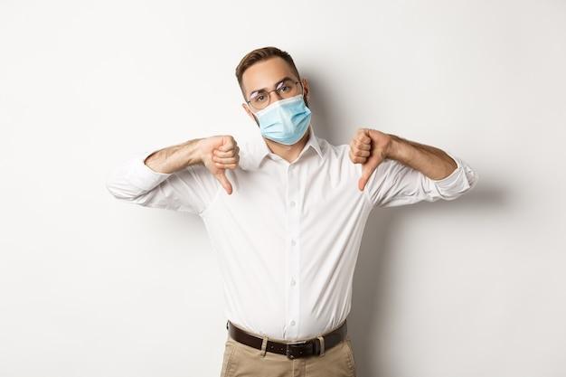 Ontevreden baas die gezichtsmasker draagt en duimen naar beneden, afkeer en afkeuringsteken, witte achtergrond toont.