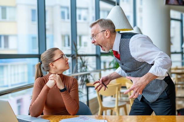 Ontevreden baas in glazen schreeuwend naar vrouwelijke manager in kantoor.
