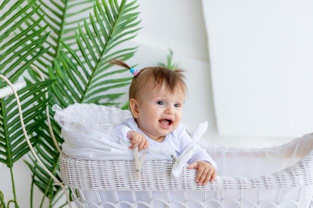 Ontevreden babymeisje zit in een witte wandelwagen thuis