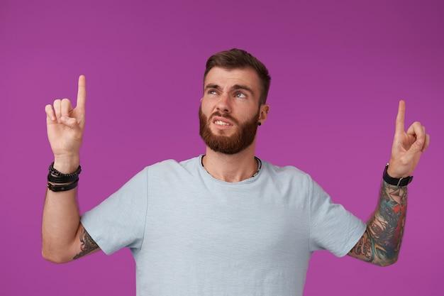 Ontevreden bebaarde getatoeëerde brunette met trendy kapsel naar boven met opgeheven wijsvingers en fronst zijn gezicht ontevreden, poseren op paars in blauw t-shirt