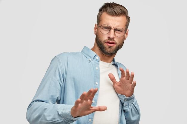 Ontevreden bebaarde man poseren tegen de witte muur