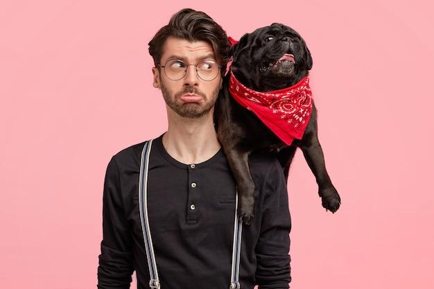 Ontevreden, bebaarde man tuit zijn lippen, kijkt met een negatieve gezichtsuitdrukking naar zijn hond, is ontevreden na een wandeling en poseert samen tegen de roze muur. mensen, dieren, relaties, levensstijl