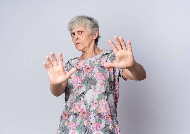Ontevreden bejaarde vrouw verdedigt het standhouden van handen die op witte muur worden geïsoleerd