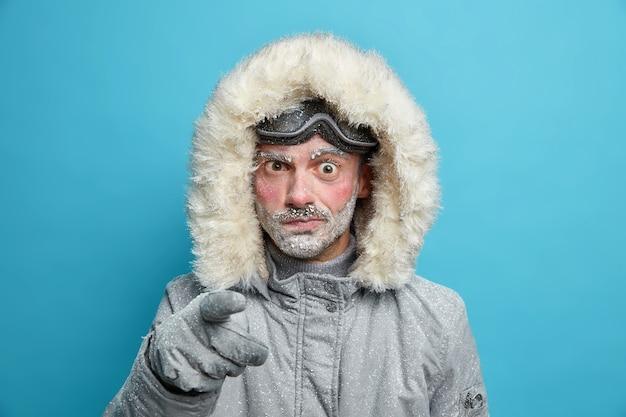 Ontevreden bevroren man met rode gezichtspunten van ontevredenheid geeft u de schuld dat u bovenkleding draagt voor koud weer zich voorbereidt op winteravontuur heeft actieve rust.