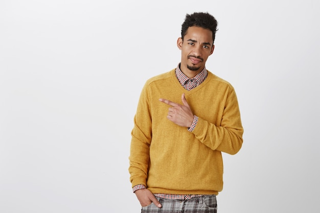 Ontevreden bezorgd jong mannelijk model met een donkere huidskleur en een afro-kapsel, wijzend naar de linkerbovenhoek, fronst en toont een afkeer
