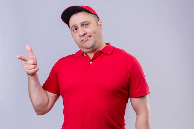 Ontevreden bezorger in rood uniform en pet met sceptische uitdrukking op gezicht wijzend met wijsvinger naar camera staan