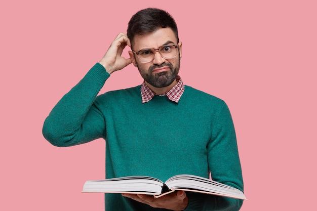 Ontevreden blanke man met dikke haren, krabt zijn hoofd van verbijstering, draagt een bril en een groene trui