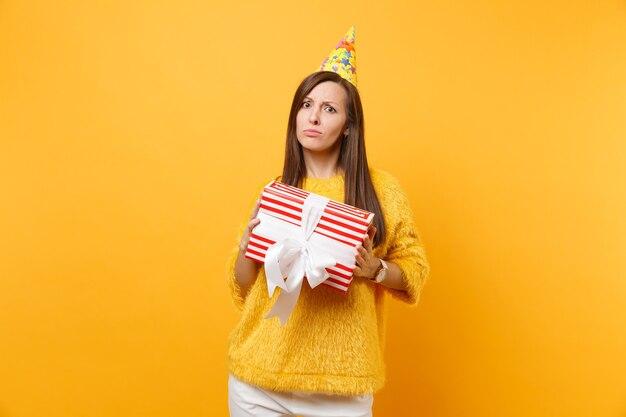 Ontevreden boos jonge vrouw in verjaardagsfeestje hoed met rode doos met cadeau, aanwezig vieren geïsoleerd op felgele achtergrond. mensen oprechte emoties, lifestyle concept. reclame gebied.