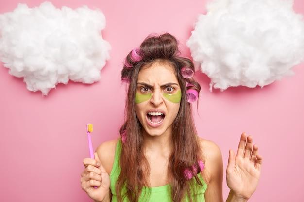 Ontevreden, boze donkerharige vrouw past haarkrulspelden toe, collageenvlekken onder de ogen om rimpels en fijne lijntjes te verminderen, houdt tandenborstel vast en heeft dagelijkse routines voor mondhygiëne geïsoleerd op roze studiomuur
