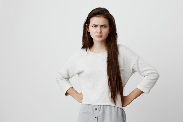 Ontevreden boze jonge vrouw in los overhemd, fronsend gezicht, met armen over elkaar, geïrriteerd en moe van studeren, weigert naar iemands woorden te luisteren. lichaamstaal en gezichtsuitdrukking