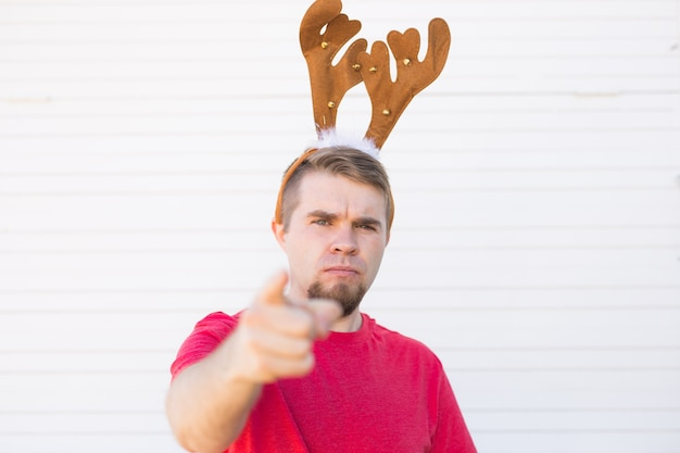 Ontevreden boze man in kerst herten hoorns wijzend op de kijker