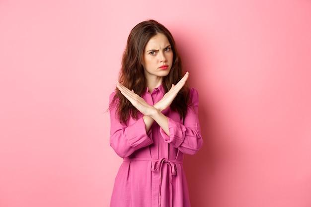 Ontevreden boze vrouw die aanbieding blokkeert, kruisstopgebaar toont, nee zegt en hoofd schudt in negatief antwoord, staande over roze muur.