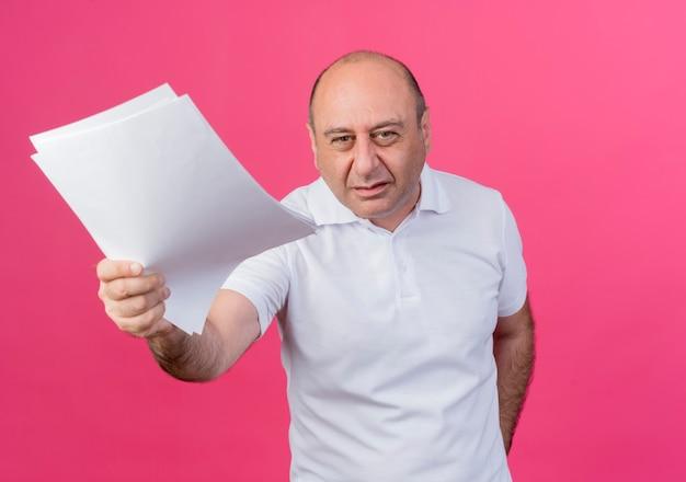 Ontevreden casual volwassen zakenman documenten uitrekken op camera geïsoleerd op roze achtergrond