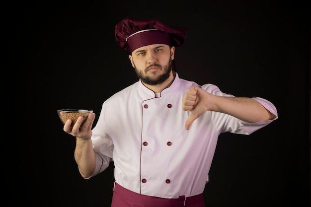 Ontevreden chef-kok man in uniform houdt transparante kom met boekweit toont afkeer teken