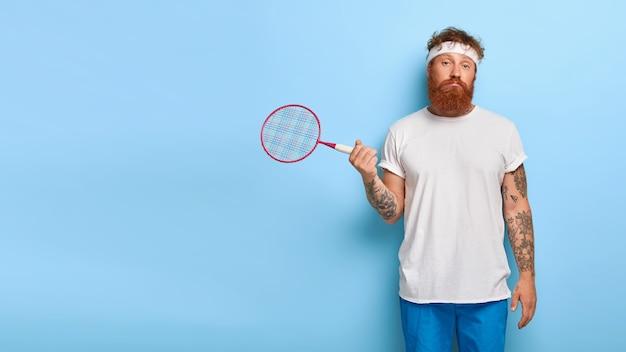 Ontevreden clueless actieve man poseert met een tennisracket, gaat sporten om zijn gezondheid te behouden