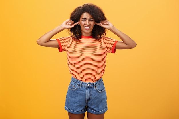 Ontevreden donkere huid meisje met krullend haar fronsen tanden op elkaar klemmen van ongemak oren sluiten met wijsvingers over oranje muur