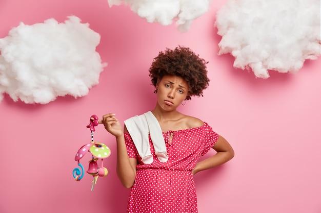 Ontevreden, droevige vrouw voelt pijn in haar rug, heeft een dikke buik, is zwanger, poseert met babyartikelen, bereidt zich voor op het moederschap, koopt kleding en speelgoed voor ongeboren kinderen, poseert tegen de roze muur