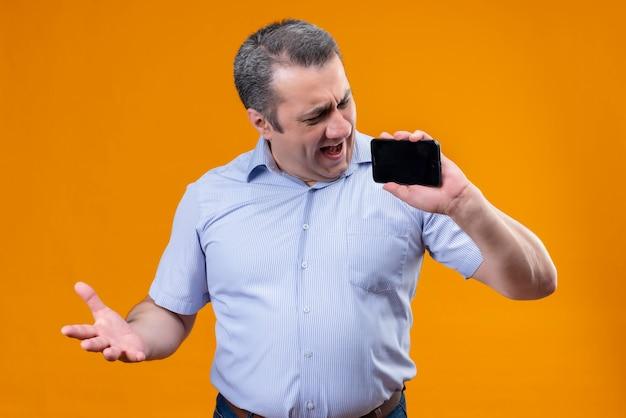 Ontevreden en boze man in blauw gestreept overhemd die zijn mobiele telefoon bekijkt terwijl hij staat