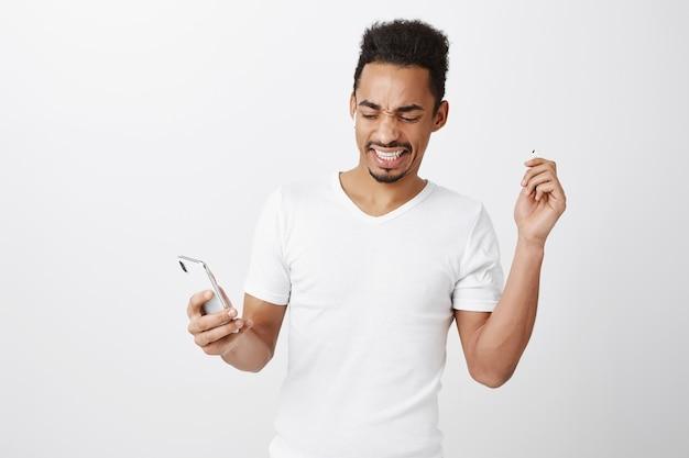 Ontevreden en gehinderd afro-amerikaanse jongen opstijgen oortelefoon van luid vreselijk geluid, stop muziek op mobiele telefoon