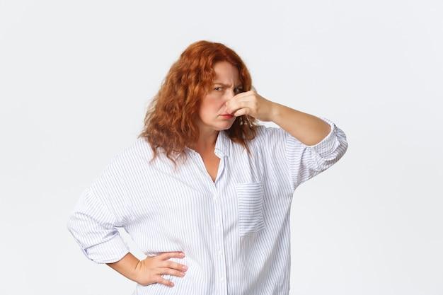 Ontevreden en ondervraagde roodharige vrouw van middelbare leeftijd die met beschuldiging naar de camera kijkt terwijl ze de neus sluit en persoon de schuld geeft voor vreselijke vreselijke geur
