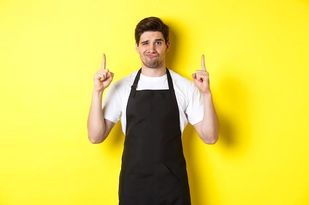 Ontevreden en sceptische ober in zwart schort wijzende vingers omhoog, uiten afkeer en onverschilligheid, staande over gele achtergrond.