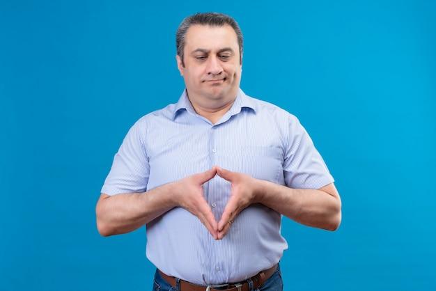 Ontevreden en verwarde man van middelbare leeftijd in blauw gestreept overhemd denken en hand in hand samen op een blauwe ruimte