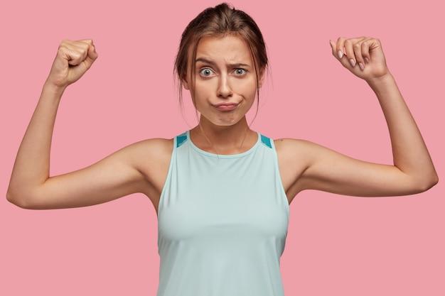 Ontevreden europees meisje fronst haar wenkbrauwen, steekt haar handen op als ze haar spieren wil laten zien