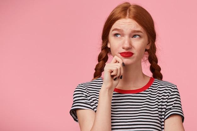 Ontevreden fronsend roodharig meisje met twee vlechten houdt vuist bij de kin en kijkt naar de linkerbovenhoek zonder verlangen, enthousiasme, ontevredenheid, is niet opgewonden met nieuw idee, op roze muur