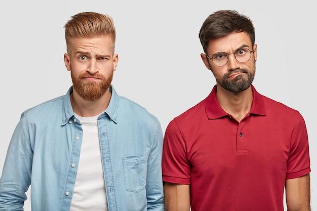Ontevreden gebaarde broers poseren tegen de witte muur