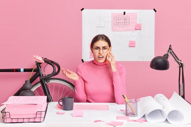 Ontevreden geërgerde vrouwelijke student van de technische afdeling werkt aan creatieve projectbesprekingen via moderne smartphone poses op desktop bespreekt met collega