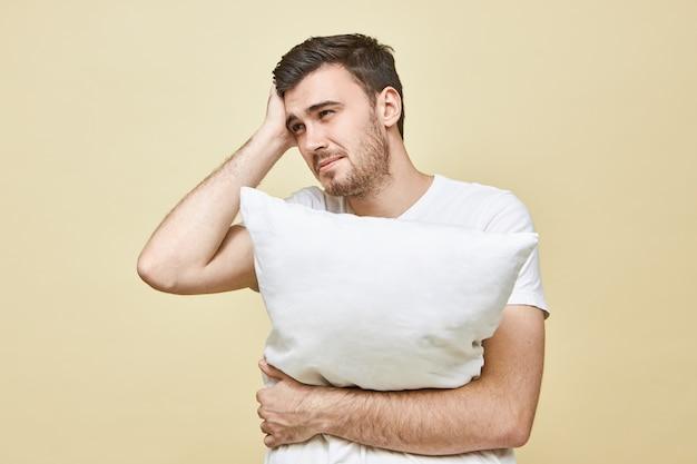 Ontevreden gefrustreerde jonge ongeschoren man die zich ziek voelt met vreselijke hoofdpijn poseren geïsoleerd, kussen knuffelend, niet slapend vanwege migraine of luidruchtige geluiden, gestreste pijnlijke blik