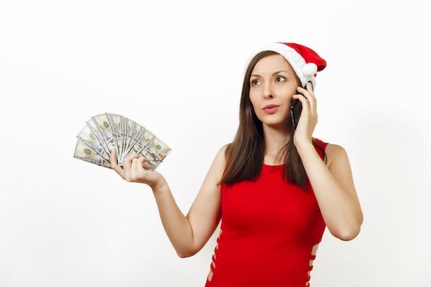 Ontevreden gefrustreerde vrouw in rode jurk en kerstmuts praten op mobiele telefoon en geld bankbiljetten te houden op witte achtergrond. santa meisje met gadget en contant geld geïsoleerd. nieuwjaarsvakantie 2018.