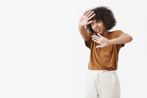 Ontevreden geïrriteerde en pissige afro-amerikaanse jonge vrouw met afro-kapsel dat beschermt tegen fel licht, met opgeheven handpalmen die het gezicht bedekken en fronst tegen ongemak
