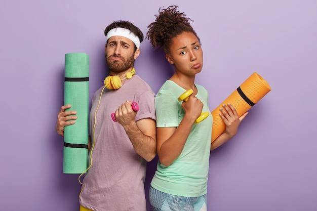 Ontevreden gemengd ras paar staan tegen elkaar, heffen zware halters op, voelen zich moe na actieve sporttraining in de sportschool, gebruiken karemat