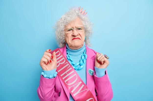 Ontevreden grijsharige vrouw portemonnees lippen heeft ontevredenheid gezichtsuitdrukking steekt handen op en bereidt zich voor op verjaardagsfeestje