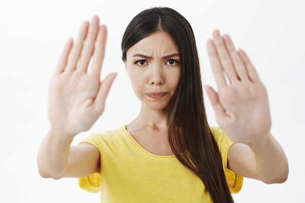 Ontevreden, intens ernstig ogende vrouw die de lippen fronst en de handpalmen opheft naar de camera in stop en verbodsgebaar