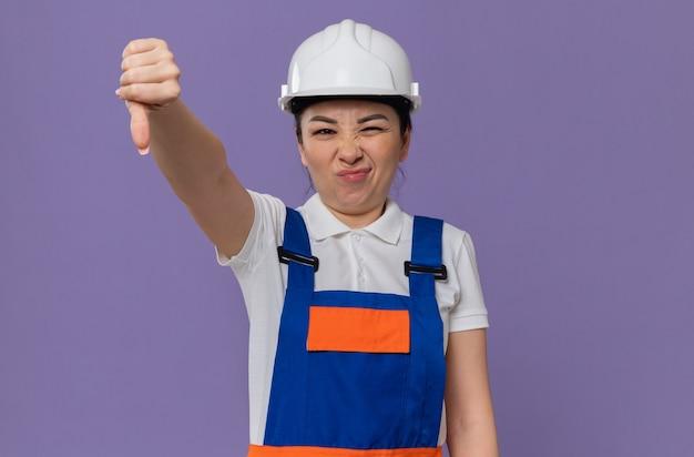 Ontevreden jong aziatisch bouwersmeisje met witte veiligheidshelm die naar beneden duimt