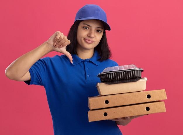 Ontevreden jong bezorgmeisje in blauw uniform en pet met pizzadozen en voedselpakket op zoek naar duimen neer staande over roze muur