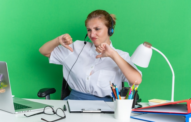 Ontevreden jong blond callcentermeisje met een hoofdtelefoon die aan het bureau zit met uitrustingsstukken die naar een laptop kijken die duimen naar beneden laat zien