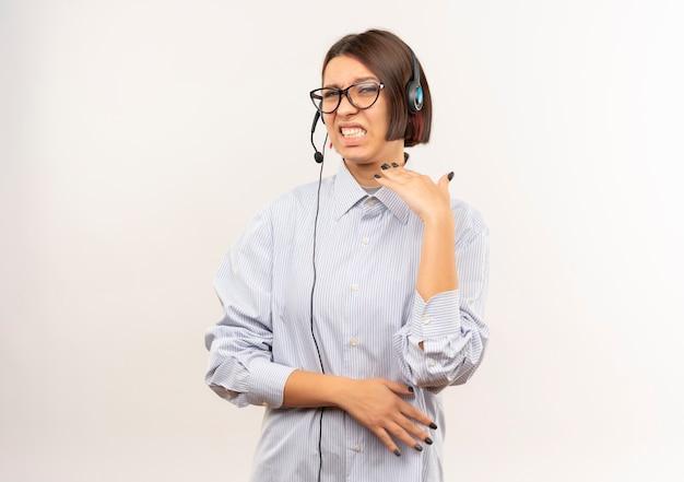 Ontevreden jong callcentermeisje die glazen en hoofdtelefoon dragen die hand op lucht houden die op witte achtergrond met exemplaarruimte wordt geïsoleerd