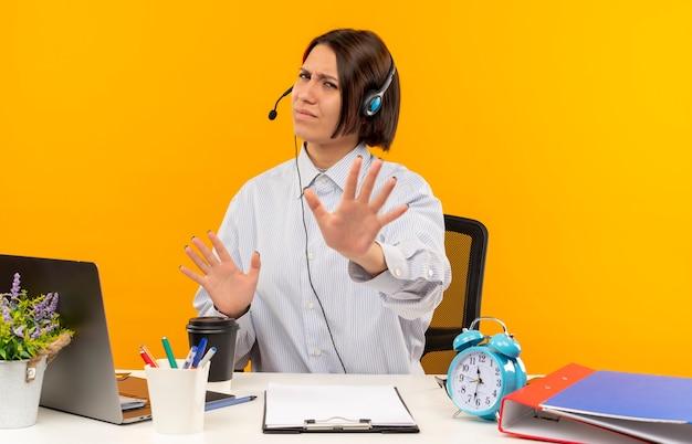 Ontevreden jong callcentermeisje die hoofdtelefoonszitting bij bureau met uitrustingsstukken dragen die geen gebaar doen dat op oranje achtergrond wordt geïsoleerd