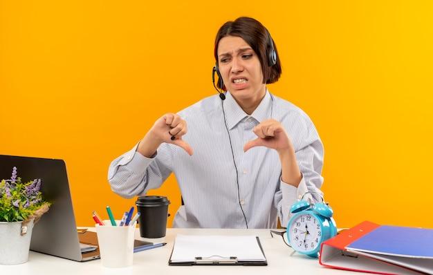 Ontevreden jong callcentermeisje die hoofdtelefoonszitting bij bureau met uitrustingsstukken dragen die laptop bekijken die duimen tonen die neer op oranje achtergrond worden geïsoleerd