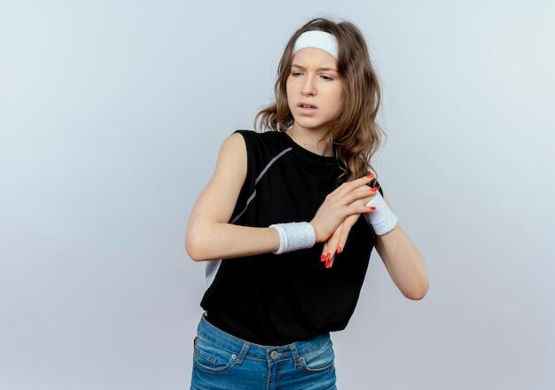 Ontevreden jong fitness meisje in zwarte sportkleding met hoofdband aanraken van haar pols pijn voelen staande over witte muur
