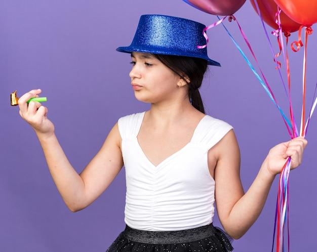 Ontevreden jong kaukasisch meisje met blauwe feestmuts met helium ballonnen en kijken naar partij fluitje geïsoleerd op paarse muur met kopie ruimte